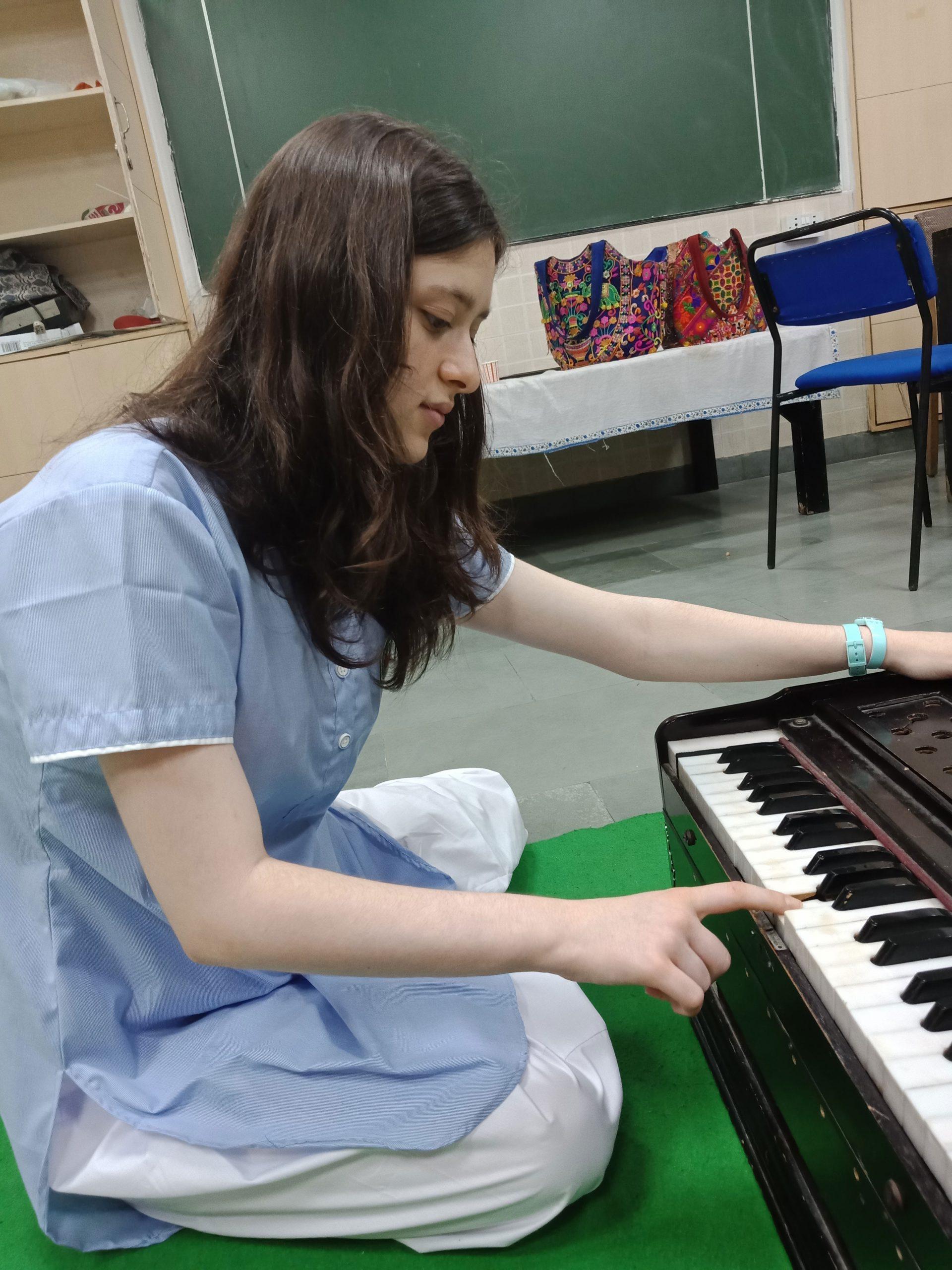 INTERNATIONAL STUDENT LEARNING TO PLAY  THE HARMONIUM